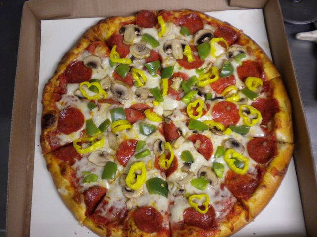Veggie pizza with olives, tomatoes, and basil made in Montrose