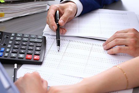 Una persona mostrando calcoli all'altra con una calcolatrice al lato