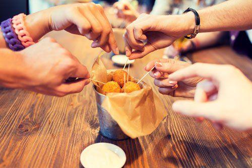 Ragazzi a tavola nel ristorante mentre prendono arancini