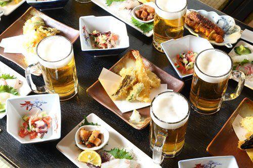 Tavola parecchiato con boccale di birra, Piattini con varietà di pesce fritti e  grigliati