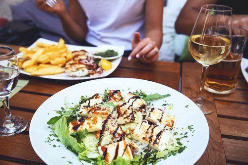 Piatto di tofu grigliato ,contorno di patate ,insalata, salsa verde, bicchiere d'acqua e di vino bianco