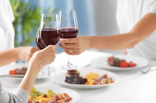 Tre persone fanno brindisi con calici di vino rosso, piatti con salumi, frutta e verdura.
