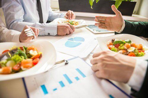 Persone sedute al tavolo mangiano un' insalata mentre parlano di lavoro