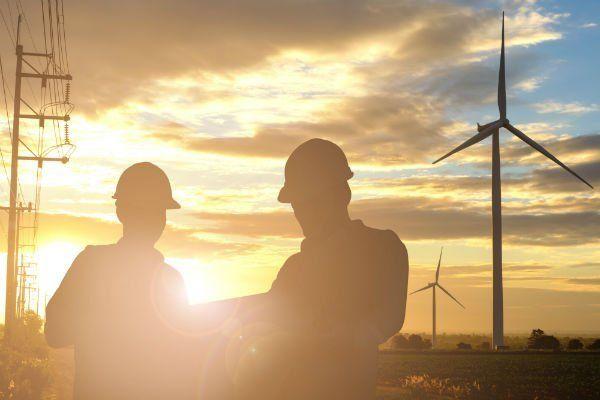 Due operatori parlando, spanditura elettrica a sinistra, mulini eolici a destra