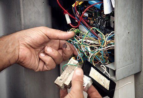 tecnico ripara una centralina d'allarme