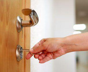 individual inserting key in lock