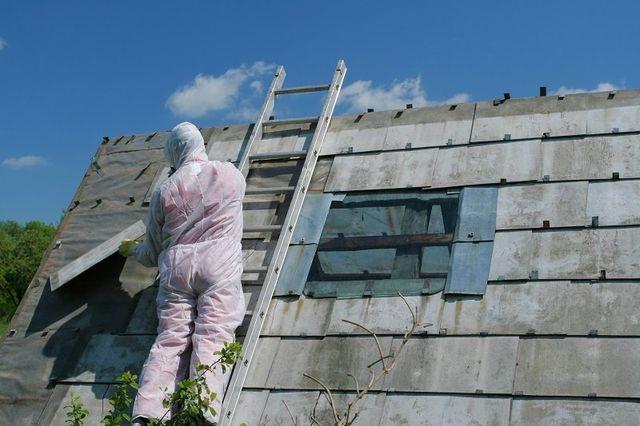 delle persone al lavoro su delle finestre con delle scale di ferro appoggiate a una facciata di una casa