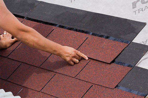 Roofing contractor placing asphalt shingles in Hauula