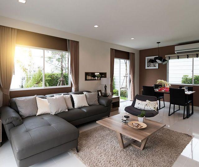 un soggiorno spazioso con sulla sinistra un divano di pelle color grigio, un tavolino di legno, una sedie imbottita e dietro un tavolo nero con delle sedie