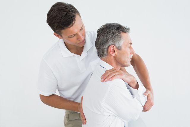 young male chiropractor helping older male patient in Kalispell