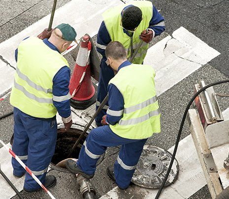 Workers moves the manhole cover to cleaning the sewer line