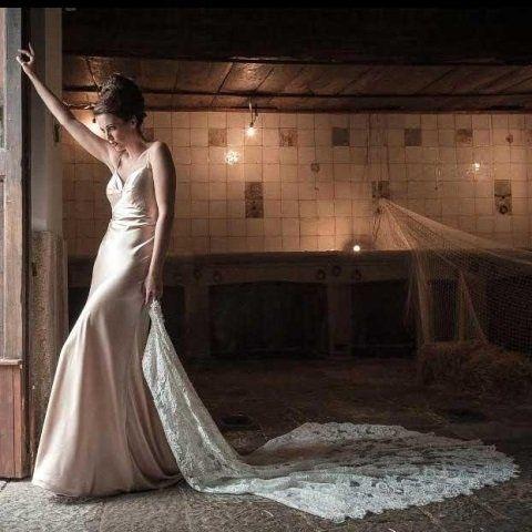 una donna con un abito da sposa con un velo lungo in mano