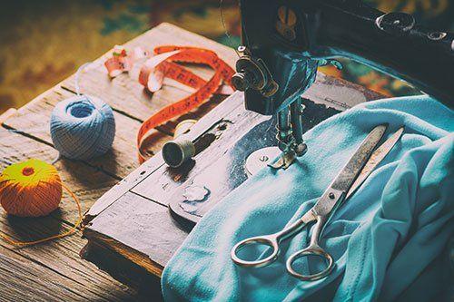 Macchina per cucire, forbici, metro e fili colorati