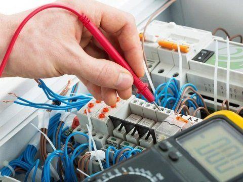 una mano con un tester e un quadro elettrico davanti