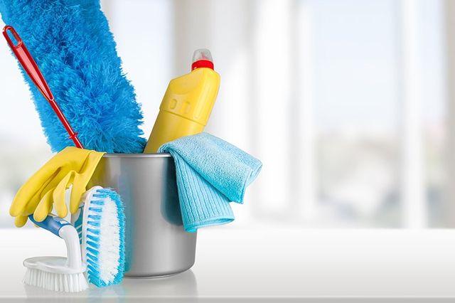 Un secchio contenente oggetti per la pulizia della casa