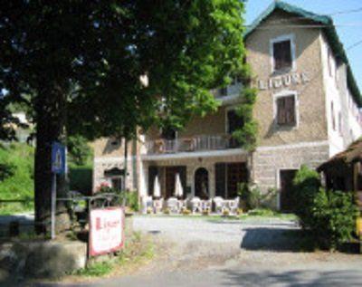 facciata dell'hotel, con alberi e sedie nello sfondo