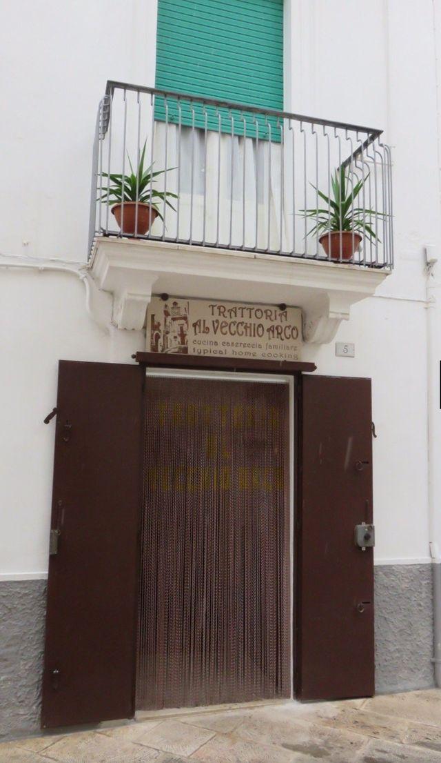 Entrata alla Trattoria Al Vecchio Arco, tenda con frange e porte in legno a Locorotondo (BA)