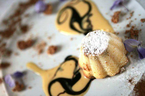 Un piatto con una tortina decorata con zucchero a velo, sciroppo al cioccolato, cacao e petali di fiori