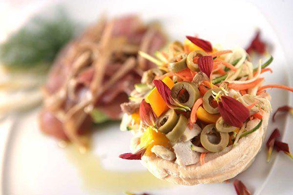 Un piatto di hamburger con verdure tagliati, olive verdi e petali di fiori