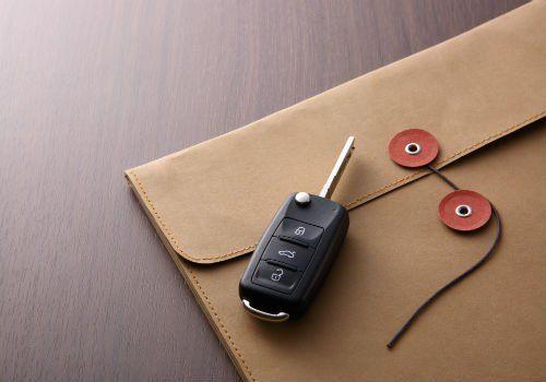 una busta di pelle e accanto delle chiavi di un'auto