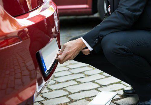 un uomo in ginocchio mentre cambia la targhetta di un'auto