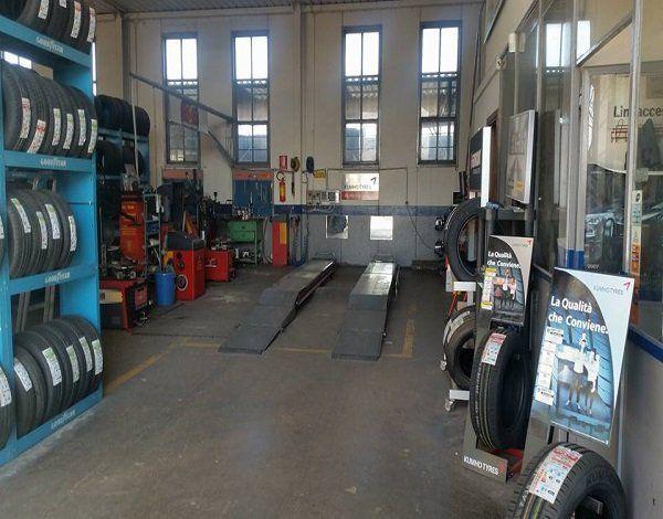 Interno del workshop, ponte, pneumatici e macchinari per cambio e taratura ruote