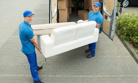 Addetti trasportano un divano bianco Traslochi e noleggi Santorso