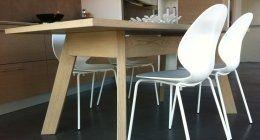 un tavolo in legno con sedie bianche