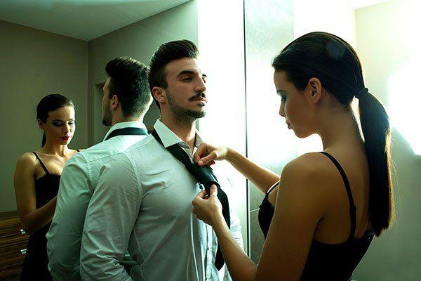 una ragazza fa il nodo alla cravatta ad un ragazzo in camicia