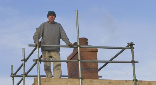 Man on roof scaffolding