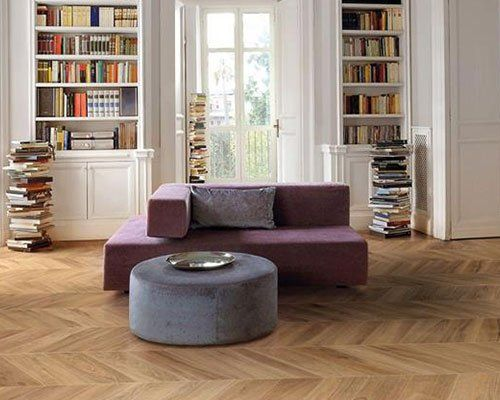 Salon con due librerie, due torri di libri chiedendo spazio, originale tavola rotonda di tessuto e un curioso sofà di due pezzi sovrapposte