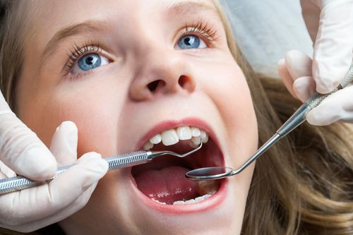 Girl getting tooth-colored filling at our dental practice in Caldwell