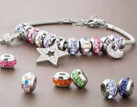 un bracciale color argento con delle stelline brillantate e oggetti di altri colori
