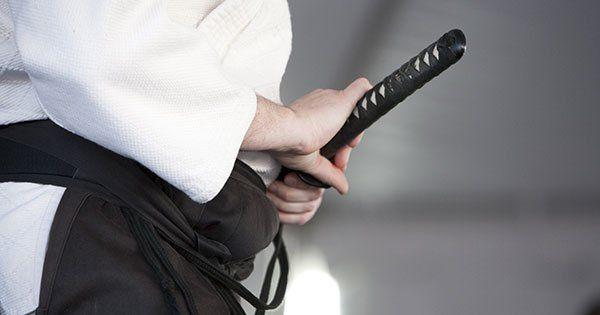 Dettaglio di una persona in kimono con una sciabola nella fondina