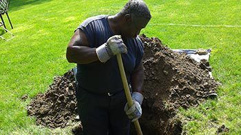 Expert septic cleaner digging in ground