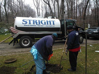 Two expert septic cleaner digging in ground