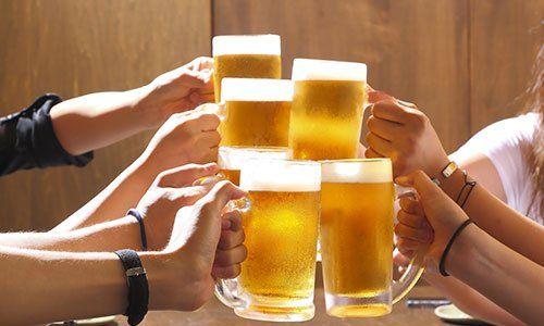 delle persone che brindano con dei boccali di birra