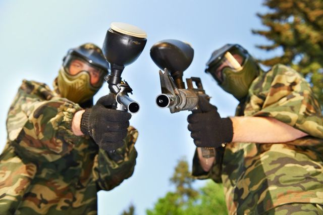 Two men pointing their paintball guns