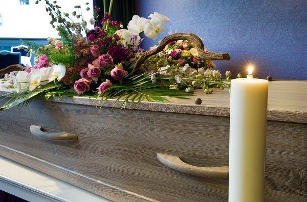 Una candela accesa accanto la bara coperta con una composizione floreale in rosa e bianco