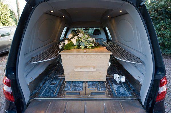 Una bara in legno chiaro all'interno del carro funebre coperta di fiori