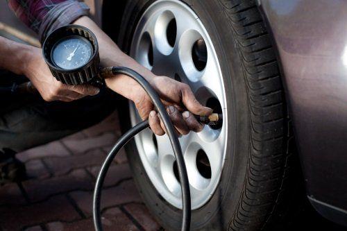 una persona verifica la pressione dei pneumatici