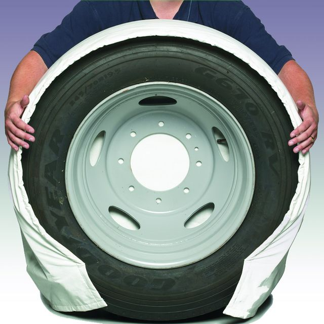 A man showing a large truck tire