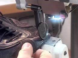 una mano tiene ferma una stoffa di color azzurro mentre la macchina da cucire sta cucendo