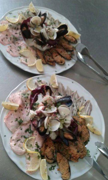 due piatti con carpaccio di pesce, vongole e le cozze gratinate