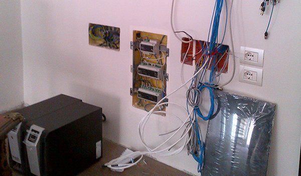 delle prese elettriche smontate con vista dei cavi elettrici di color blu e bianchi in uno stanzino