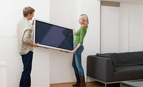 Two people holding TV