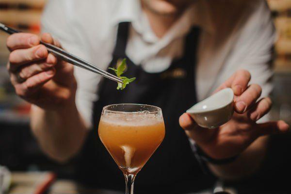 barman prepara un cocktail arancione con della menta
