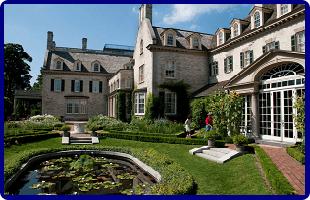 a country estate house with a green garden