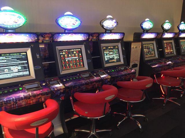 una mano che inserisce una banconota in una slot machine