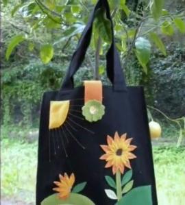 una borsa di color nero con dei disegni dei fiori arancioni